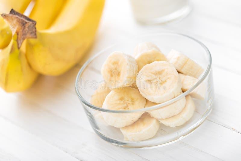 Свежие отрезанные бананы на белом деревянном крупном плане предпосылки стоковые изображения rf