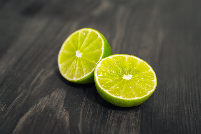 Свежие отрезанные известка, лимон и соль на деревянной таблице стоковая фотография