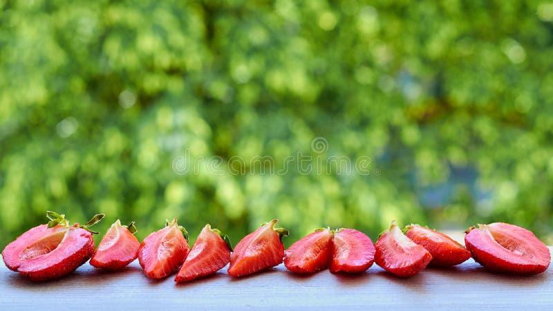 Свежие отрезанные клубники близко вверх на сером кухонном столе Ингридиенты для smoothie или здорового коктеиля лета стоковая фотография