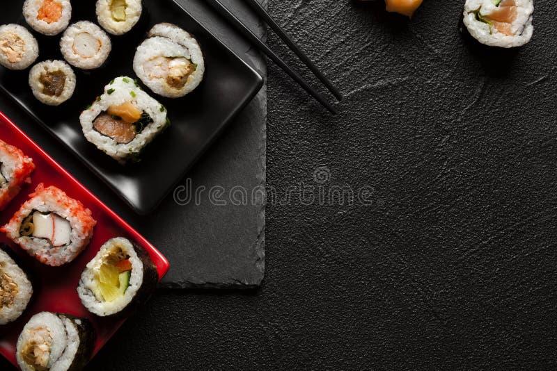 Свежие очень вкусные суши установленные на черную таблицу стоковое изображение rf