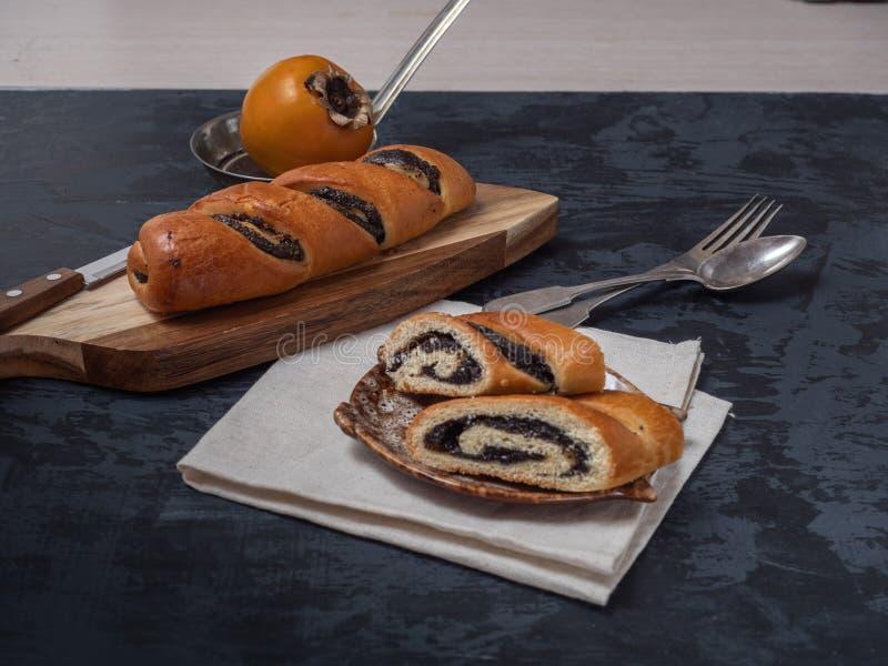 Свежие пекарня и хурма на декоративных плитах, серебряный столовый прибор, против темной предпосылки Конец-вверх стоковая фотография rf