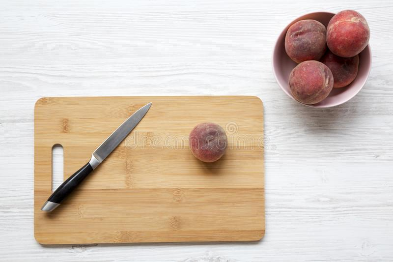 Свежие персики в розовом шаре Нож и один персик на разделочной доске над белой деревянной предпосылкой стоковая фотография rf