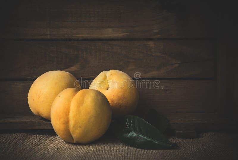 Свежие персики на деревянной доске стоковое изображение