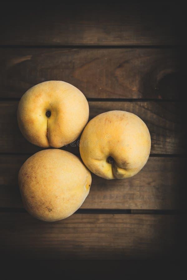 Свежие персики на деревянной доске стоковое фото