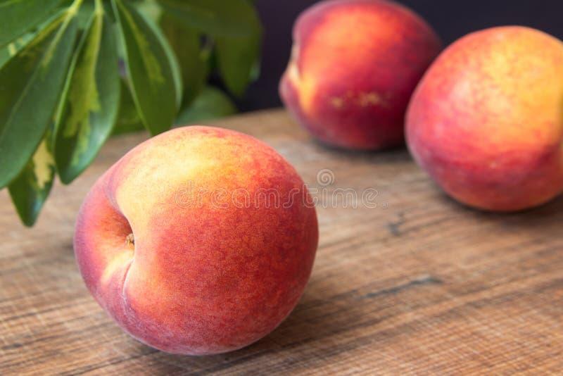 Свежие персики на деревянной разделочной доске стоковое фото