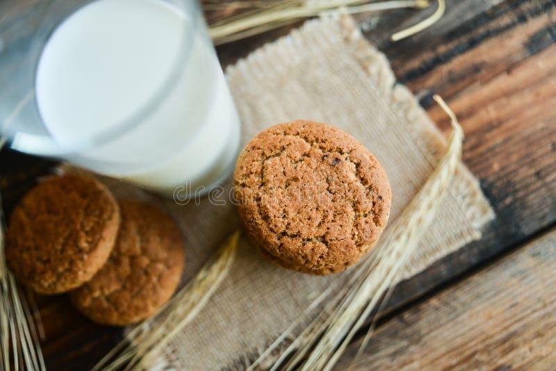 свежие печенья и молоко овсяной каши на деревянной предпосылке с шипами овсов стоковая фотография
