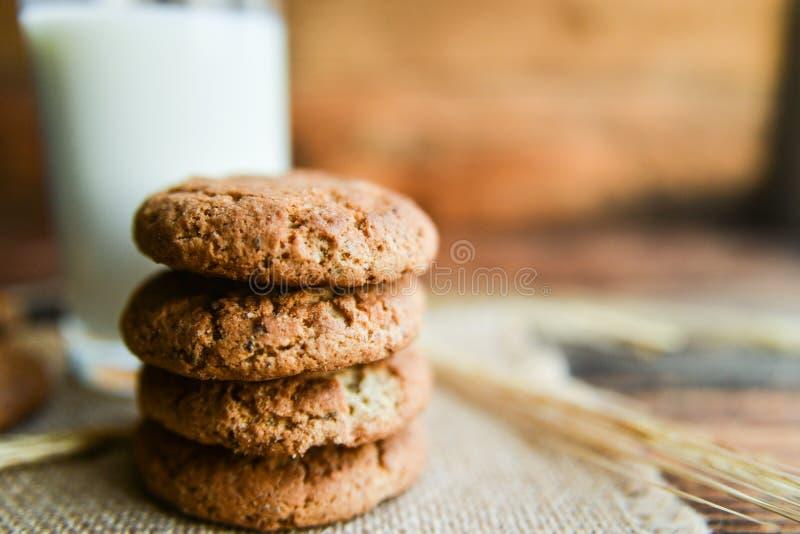 свежие печенья и молоко овсяной каши на деревянной предпосылке с шипами овсов стоковое фото rf