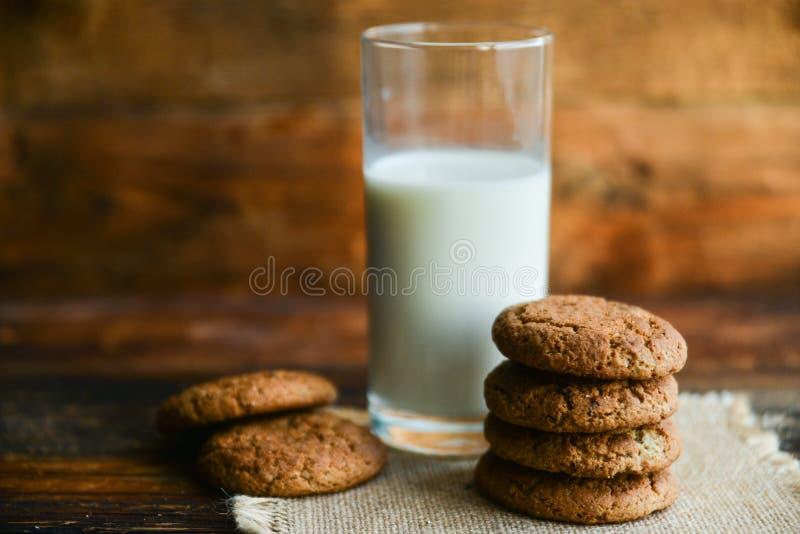 свежие печенья и молоко овсяной каши на деревянной предпосылке с шипами овсов стоковая фотография rf