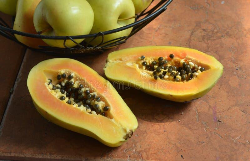Свежие половины папапайи отрезка с черными семенами, корзиной провода яблок стоковое фото