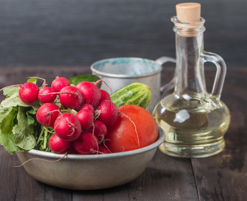 Свежие редиски, томаты, огурцы и оливковое масло стоковое фото