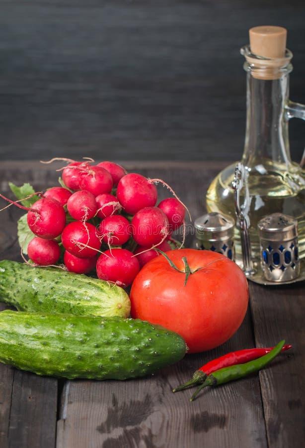 Свежие редиски, томаты, огурцы и оливковое масло стоковое фото rf