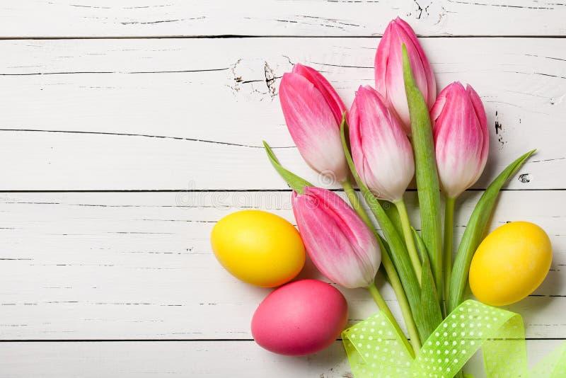 Свежие розовые тюльпаны и пасхальные яйца на деревянной предпосылке стоковые фотографии rf