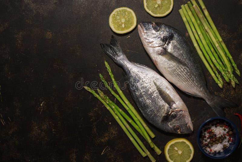 Свежие рыбы dorado со спаржей и специями, ингредиентами для варить на темной предпосылке Взгляд сверху, место для текста, плоског стоковые изображения