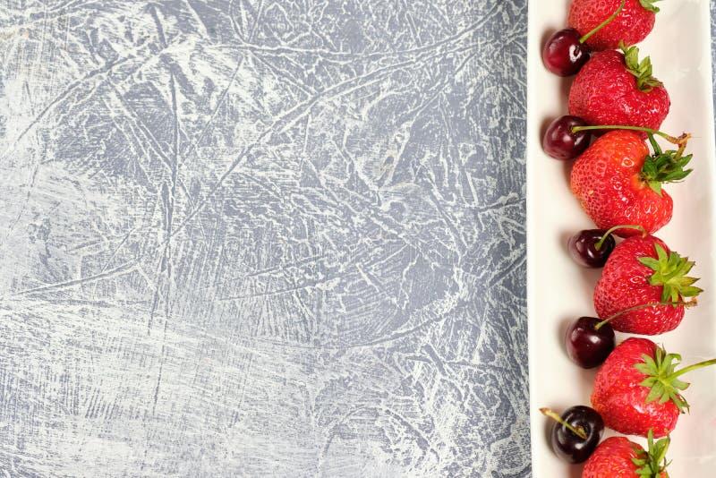 Свежие сладкие вишни и клубники на белой плите здоровая еда, витамины на серой таблице стоковые изображения