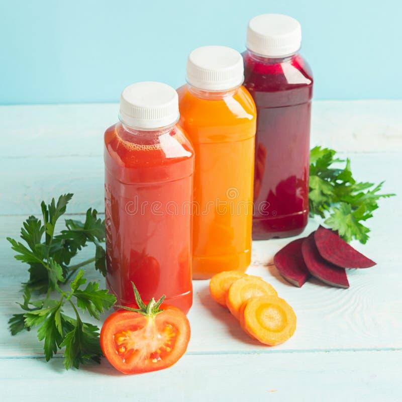 Свежие соки смузи из различных овощей морковь яблочные помидоры свеклы в бутылках на деревянном синем фоне стоковые фотографии rf