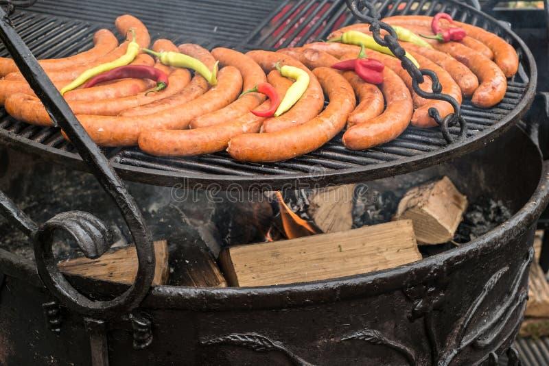 Свежие сосиски и перцы на гриле с древесиной стоковое фото