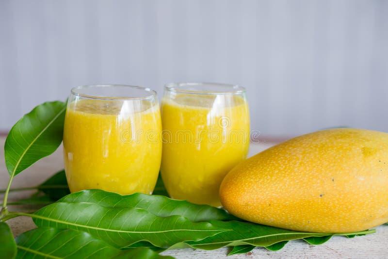 Свежие стекла сока манго и зеленые лист, тропическое питье лета стоковые фото
