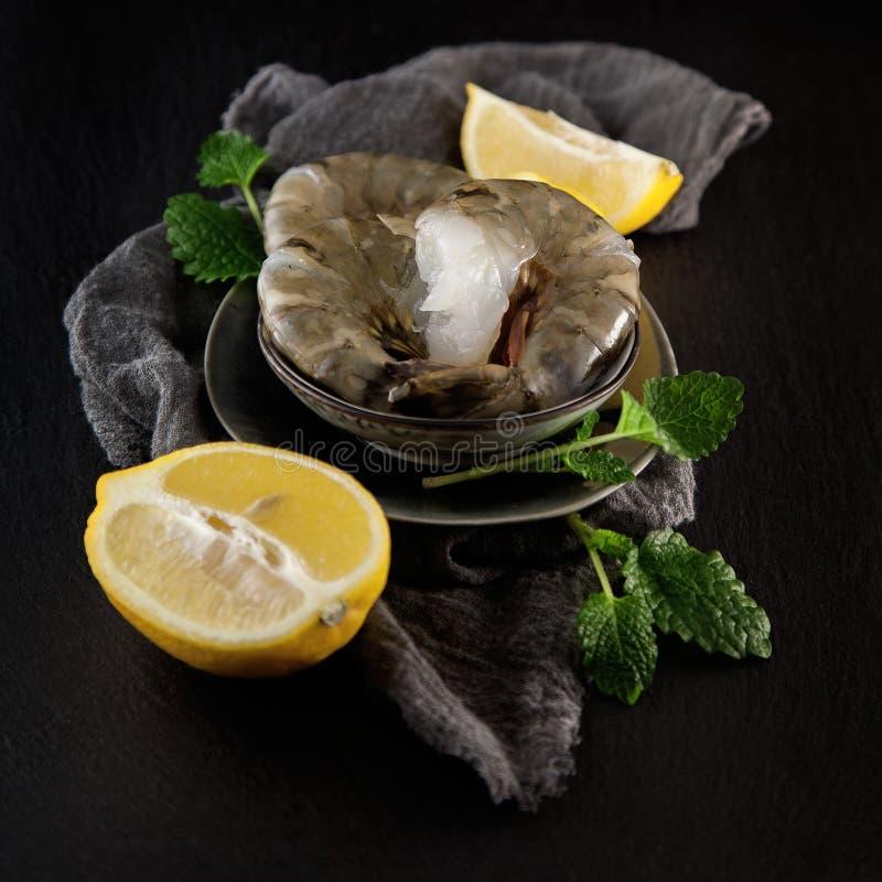 Свежие сырцовые королевские креветки с лимоном и бальзамом лимона на темной плите кухни шифера стоковое фото rf