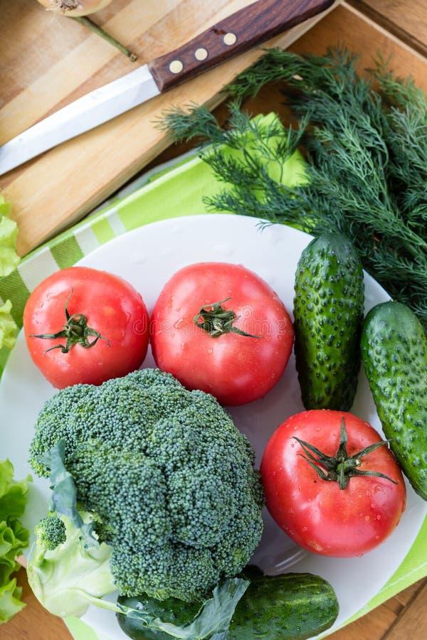 Свежие сырцовые овощи на белой плите на деревянном столе стоковые фотографии rf