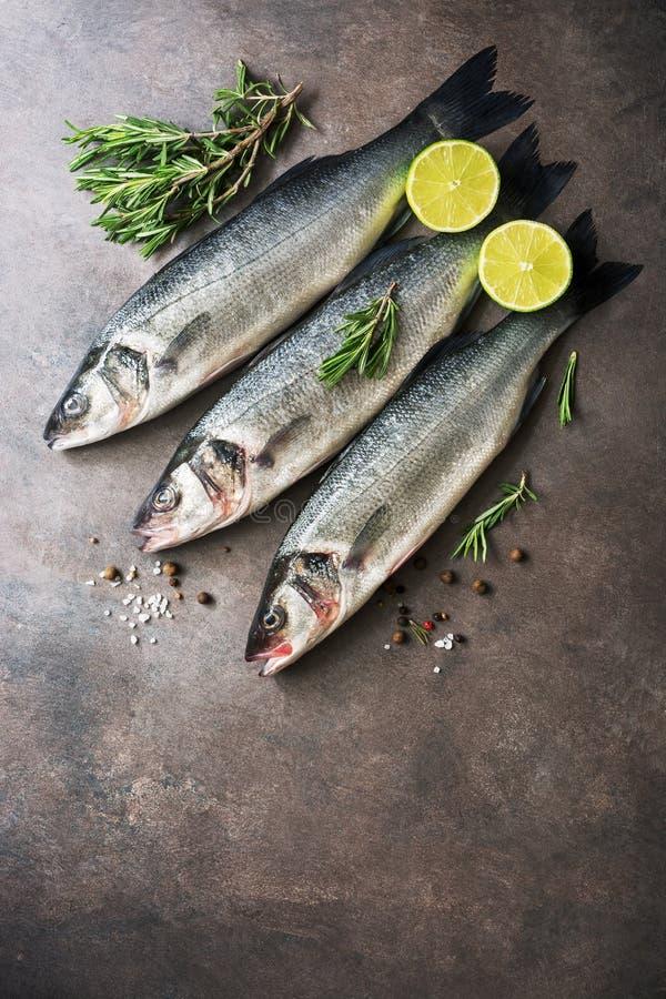 Свежие сырцовые рыбы морского окуня с розмариновым маслом и известкой на темной коричневой деревенской предпосылке ( стоковое фото rf