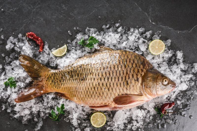 Свежие сырцовые рыбы со специями, лимон карпа зеркала на льде над темн стоковые фотографии rf
