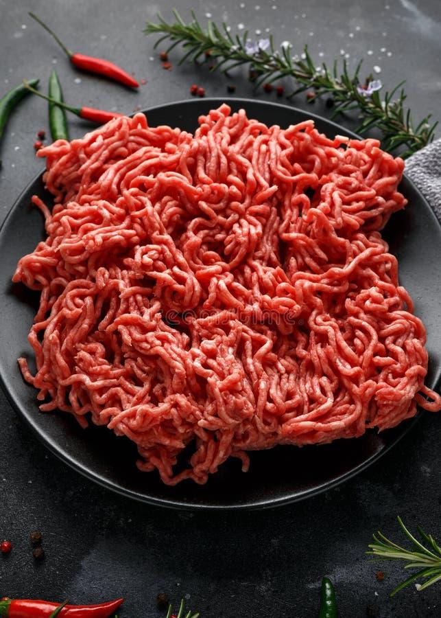 Свежие сырцовые семенят, семенить говядина, земное мясо с травами и специи на черной плите стоковая фотография rf