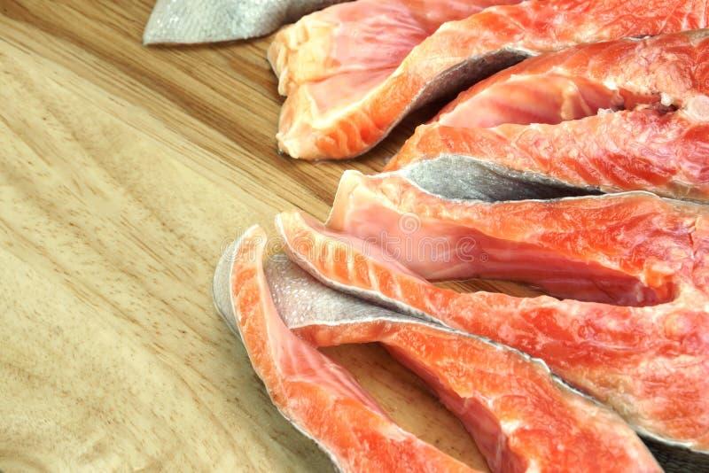 Свежие сырцовые Salmon стейки рыб на деревянной разделочной доске стоковые изображения