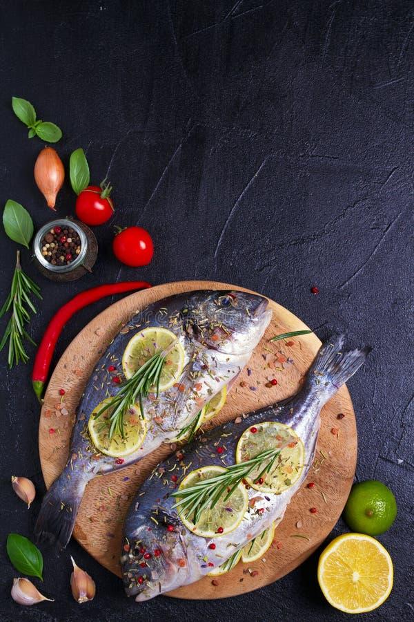 Свежие сырые рыбы леща dorado или моря с лимоном, травами, овощами и специями на черной предпосылке стоковое изображение