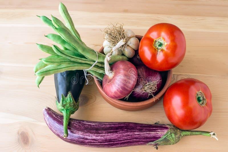 Свежие томаты, баклажаны, зеленые фасоли, луки и чеснок на a стоковые фотографии rf