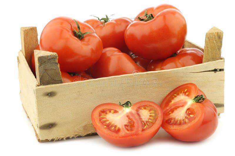Свежие томаты говядины и отрезанное одно в деревянной клети стоковое изображение