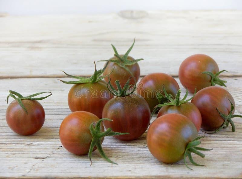Свежие томаты красной и черной вишни светлая деревянная предпосылка стоковая фотография rf