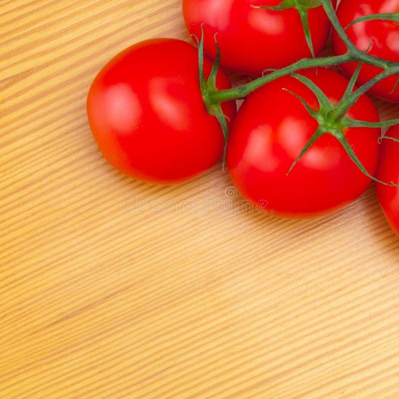 Свежие томаты на деревянном столе - взгляде от верхней части стоковые изображения