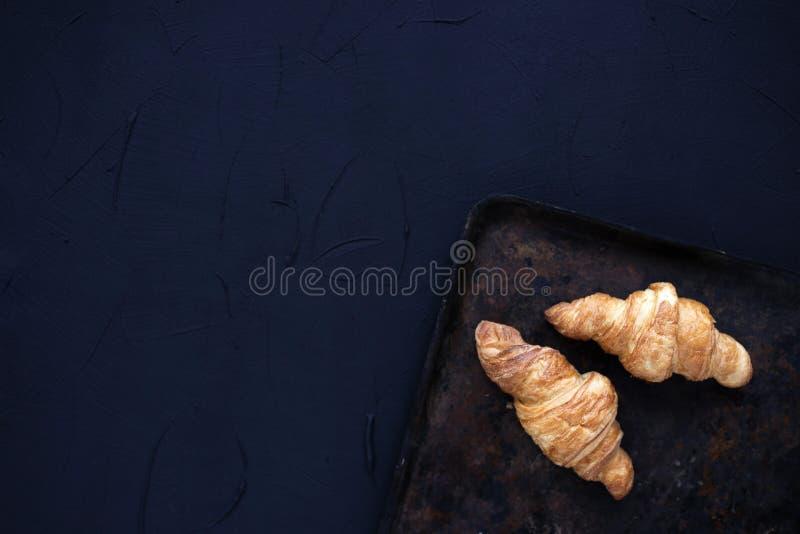 Свежие традиционные французские круассаны на винтажной темной предпосылке Надземный взгляд стоковые фотографии rf