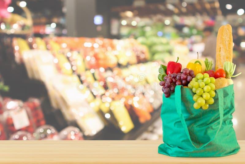 Свежие фрукты и овощи в хозяйственной сумке на деревянной столешнице с супермаркетом стоковые изображения