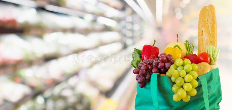 Свежие фрукты и овощи в хозяйственной сумке с предпосылкой супермаркета запачканной гастрономом defocused стоковое фото rf