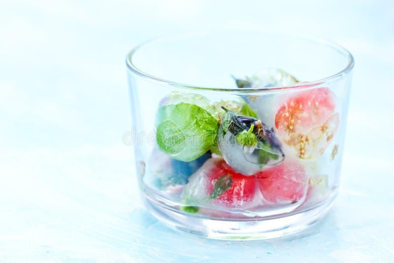 Свежие фрукты и ягода, который замерли в кубах льда на голубой предпосылке f стоковое изображение rf
