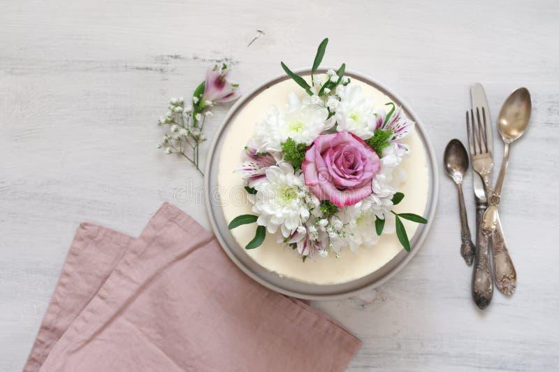 Свежие цветки украсили белый торт стоковое фото