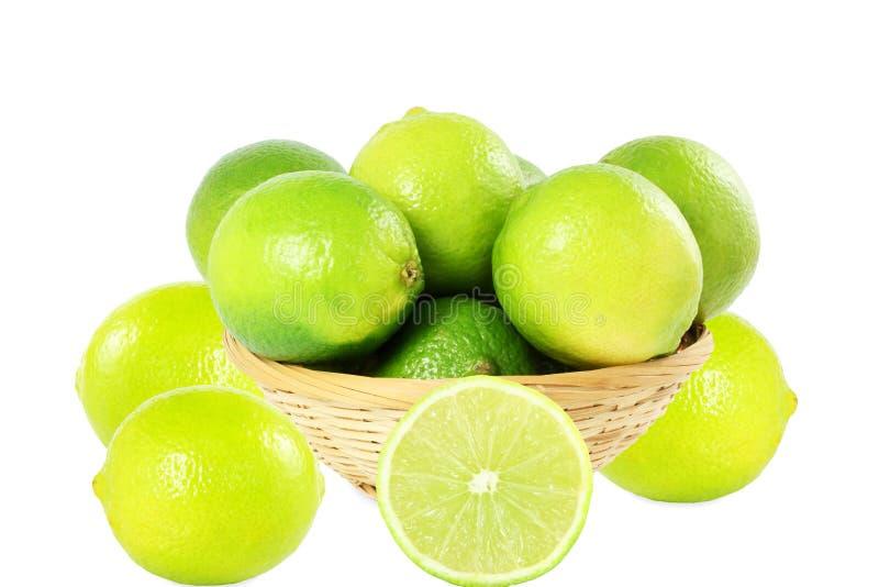 Свежие цитрусовые фрукты известки лимона в бамбуковой корзине в белой предпосылке стоковое фото rf