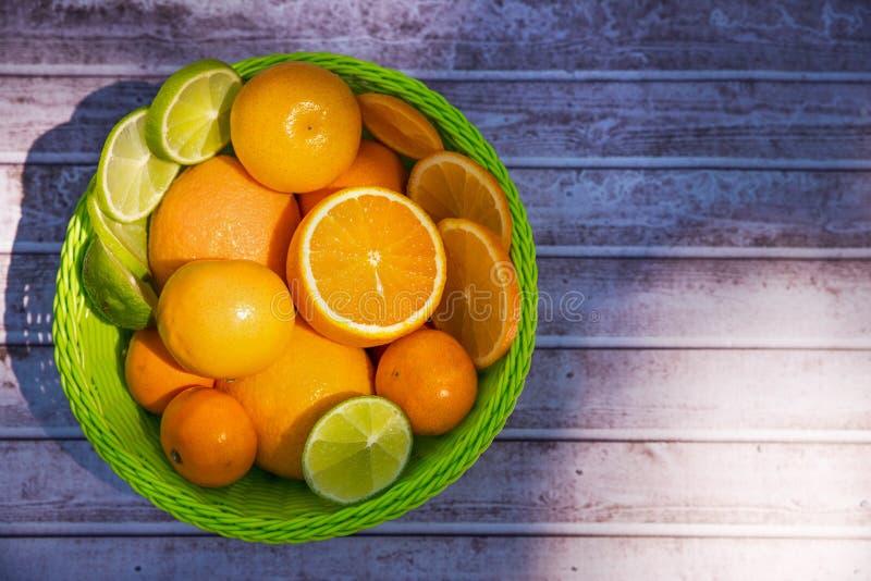 Свежие цитрусовые фрукты с зелеными листьями в плетеной корзине на деревянной предпосылке стоковые фото