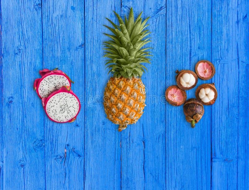 Свежие экзотические плоды, аранжированные на голубой предпосылке Розовый плод дракона, желтый ананас и пурпурный мангустан стоковое фото