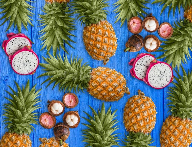 Свежие экзотические плоды, аранжированные на голубой предпосылке Розовый плод дракона, желтый ананас и пурпурный мангустан стоковые фотографии rf