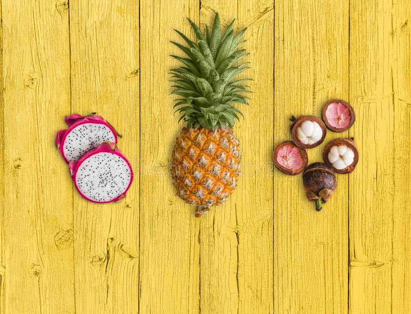Свежие экзотические плоды, аранжированные на желтой предпосылке Розовый плод дракона, желтый ананас и пурпурный мангустан стоковая фотография rf