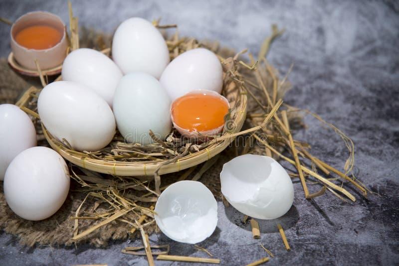 Свежие яйца утки в соломе и соли на корзине для делать посоленные яйца для детей, консервации яйца Сломленное яйцо над белизной стоковые фото