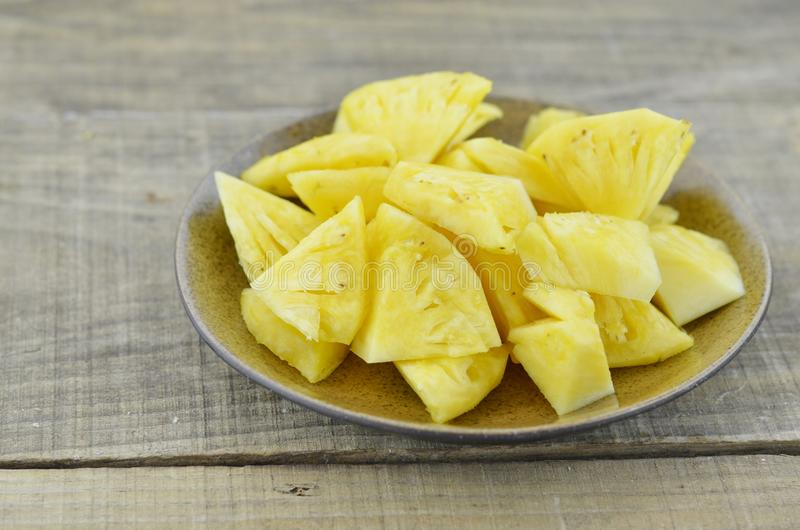 Свежий ананас отрезал куски в коричневой плите на деревянной предпосылке стоковая фотография rf