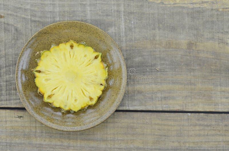 Свежий ананас отрезка в коричневой плите на деревянной предпосылке стоковые изображения rf