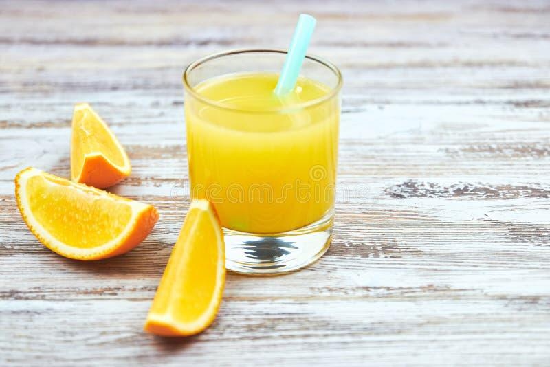 Свежий апельсиновый сок в стеклянных и оранжевых кусках на затрапезном свете таблицы o r : Цитрус космоса экземпляра стоковые фотографии rf