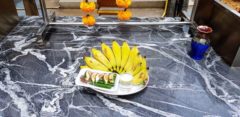 Свежий банан, небольшое стекло воды и бетэл - гайка в белом блюде на черной мраморной таблице стоковые изображения rf