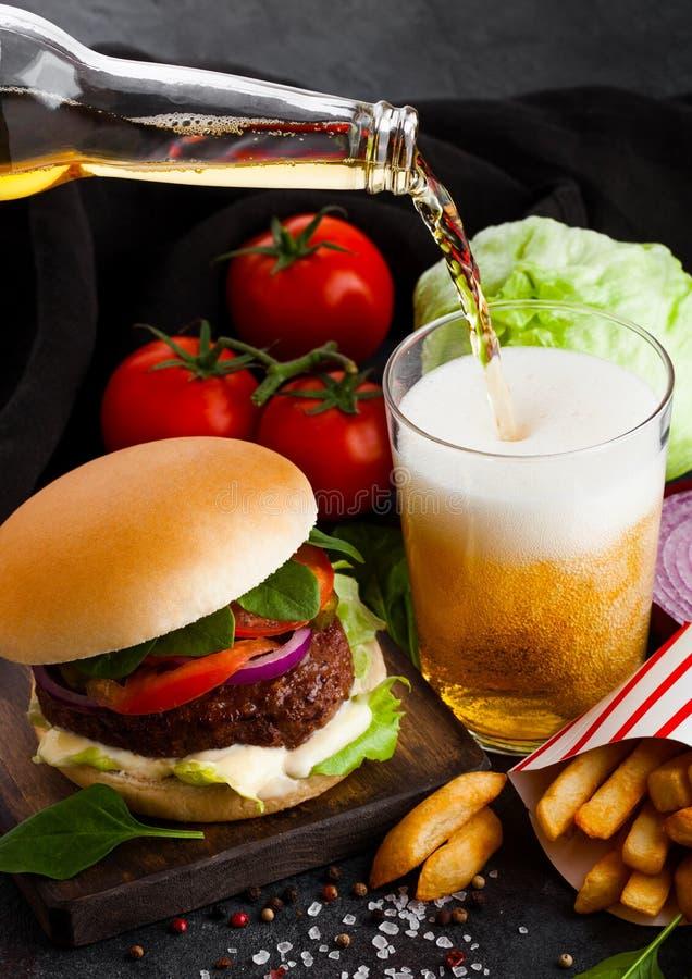 Свежий бургер говядины с соусом и овощами и стеклом пива ремесла лагера с картофелем фри картофельных чипсов на каменном backgrou стоковые изображения rf