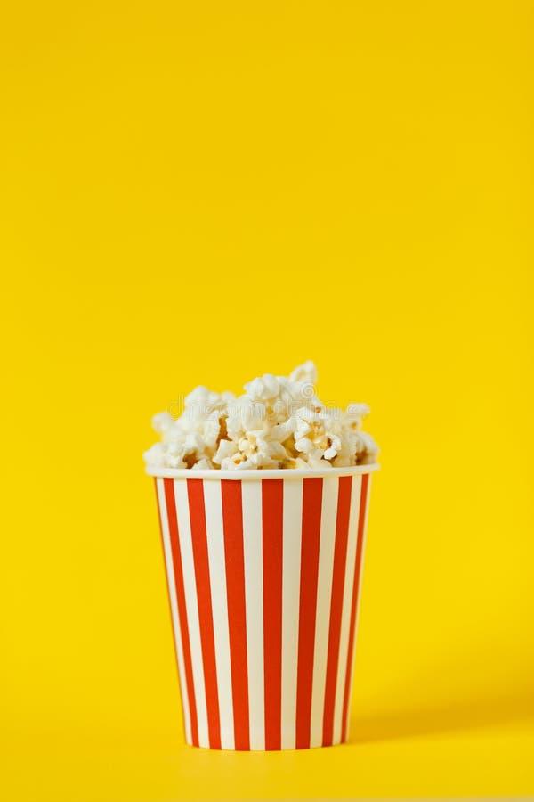 Свежий вкусный попкорн и красная чашка на предпосылке цвета желтой, взгляде со стороны с космосом для текста Закуска кино стоковые изображения
