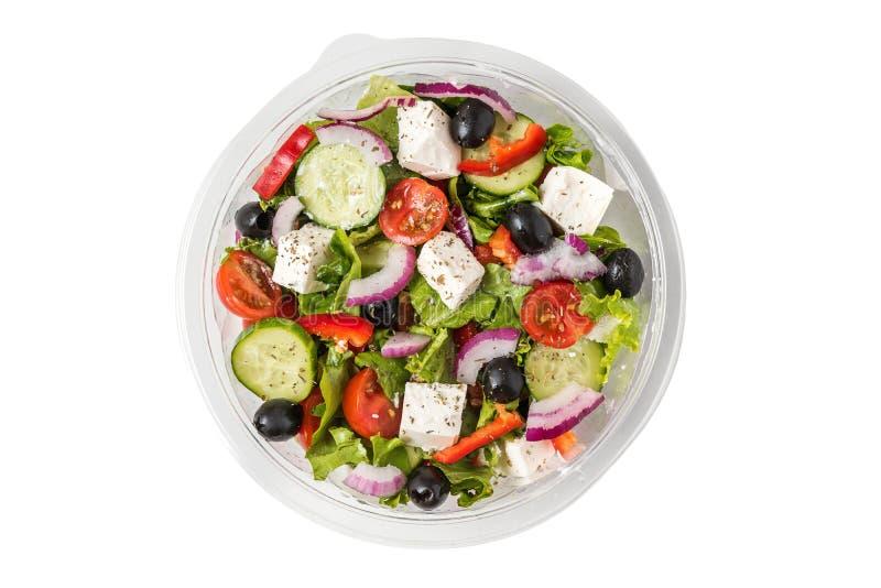 Свежий греческий салат в пластиковом пакете, который нужно принять прочь на обед изолированный на белой предпосылке стоковые фото